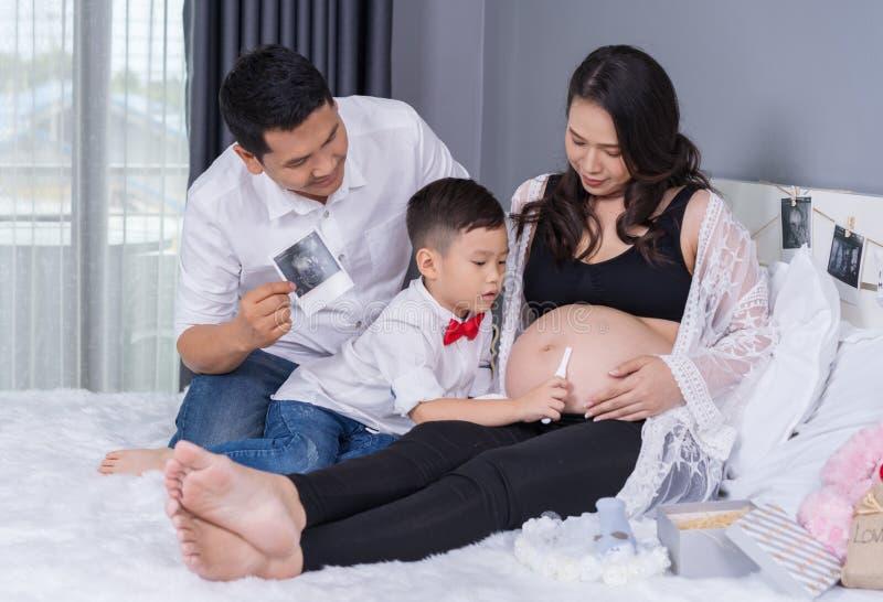 幸福家庭概念、怀孕的母亲、父亲和儿子有妊娠试验的在床上 免版税库存图片