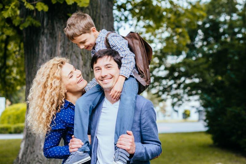 幸福家庭母亲,父亲和他学生儿子使用室外在公园 库存照片