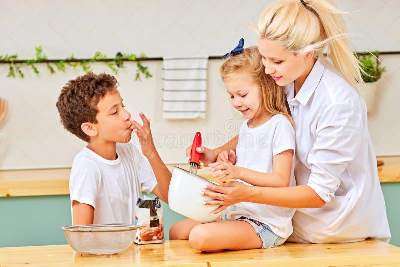 幸福家庭滑稽的孩子和妈妈在厨房里准备面团,烘烤曲奇饼 库存图片