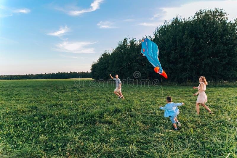 幸福家庭父亲、母亲和儿童儿子发射在自然的一只风筝在日落 库存照片