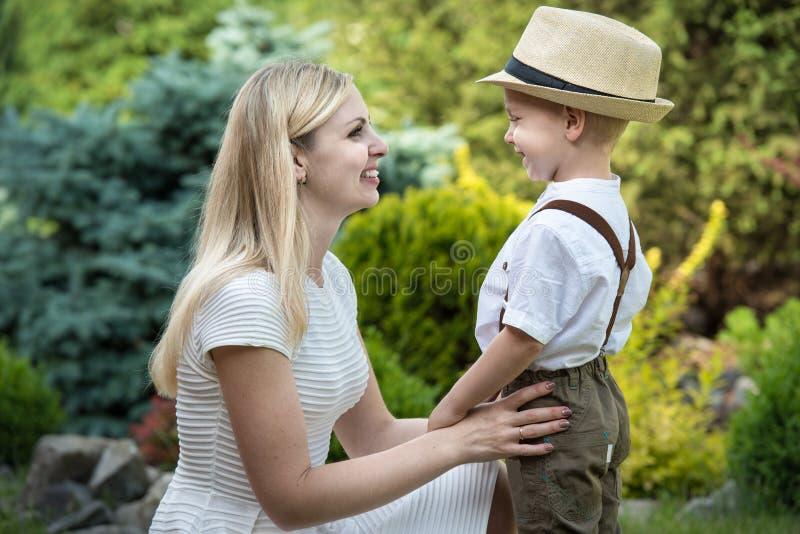 幸福家庭的生活片刻!一起使用母亲和儿子的孩子获得乐趣在草在晴朗的夏日 图库摄影