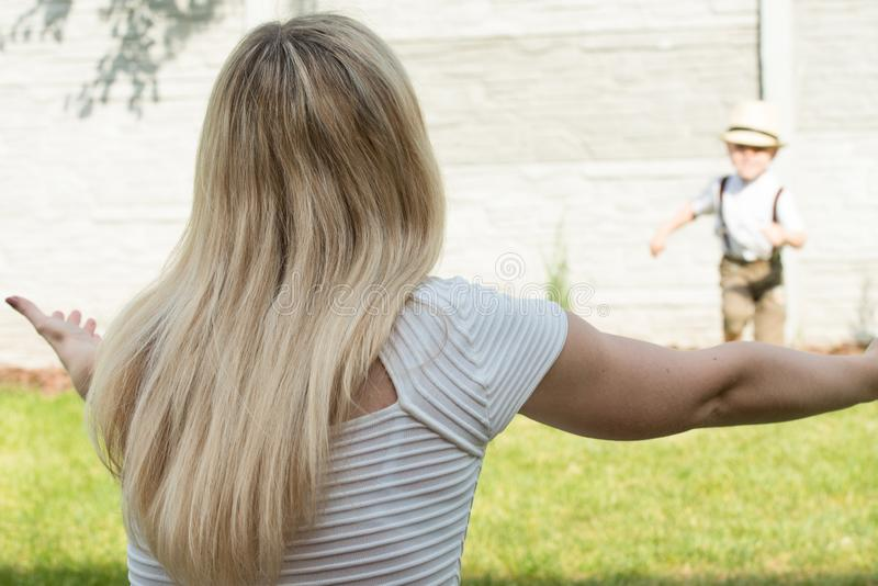 幸福家庭的生活片刻!一起使用母亲和儿子的孩子获得乐趣在草在晴朗的夏日 免版税库存图片