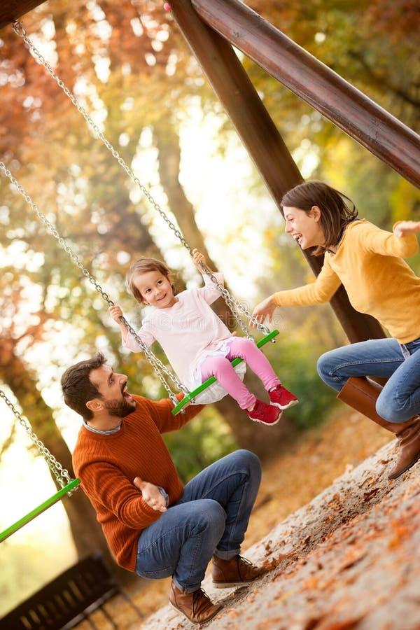 幸福家庭获得在摇摆乘驾的乐趣在庭院一秋天天 库存照片