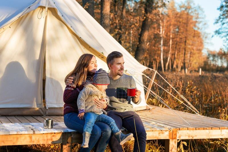 幸福家庭饮用的咖啡,当坐在帆布钟形帐幕附近在森林里时 库存照片
