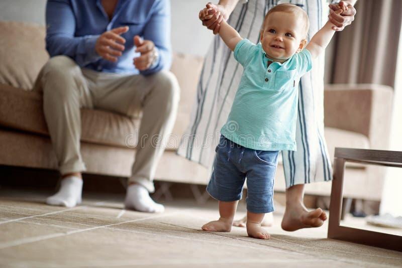 幸福家庭-做第一步的微笑的男婴 免版税图库摄影
