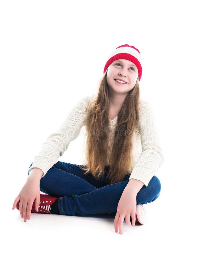 幸福寒假圣诞节 少年概念-微笑的年轻女人红色帽子的,围巾和在白色背景 图库摄影