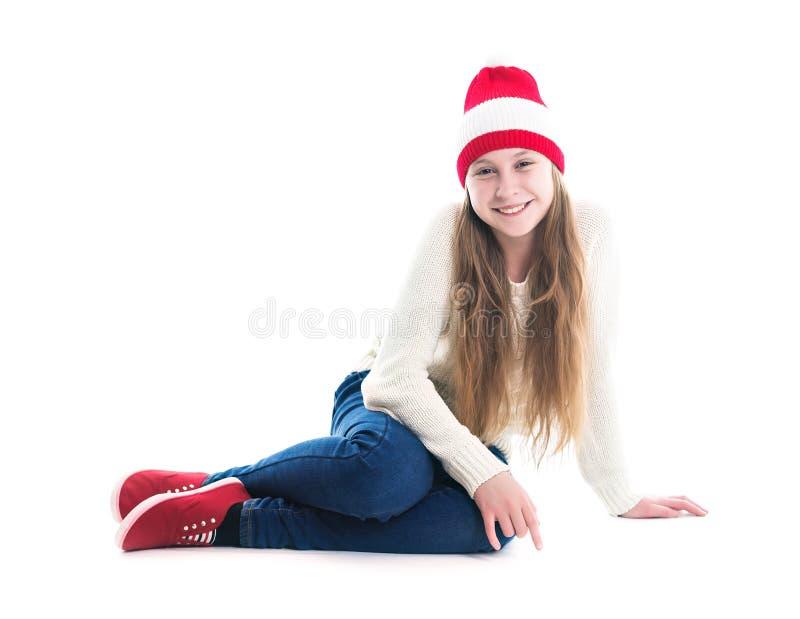 幸福寒假圣诞节 少年概念-微笑的年轻女人红色帽子的,围巾和在白色背景 库存照片