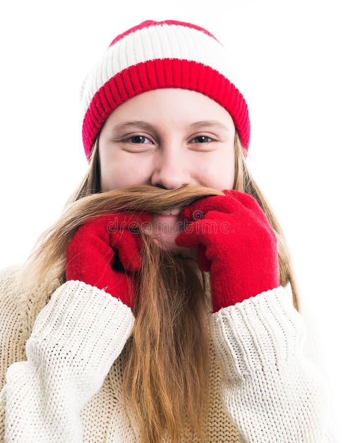 幸福寒假圣诞节 少年概念-微笑的年轻女人红色帽子的,围巾和在白色背景 免版税库存图片