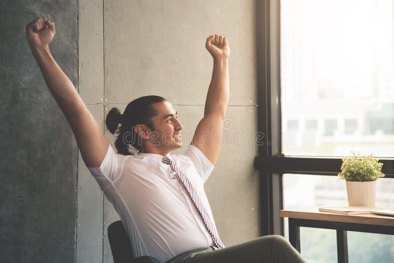 幸福年轻商人坐椅子 免版税库存照片