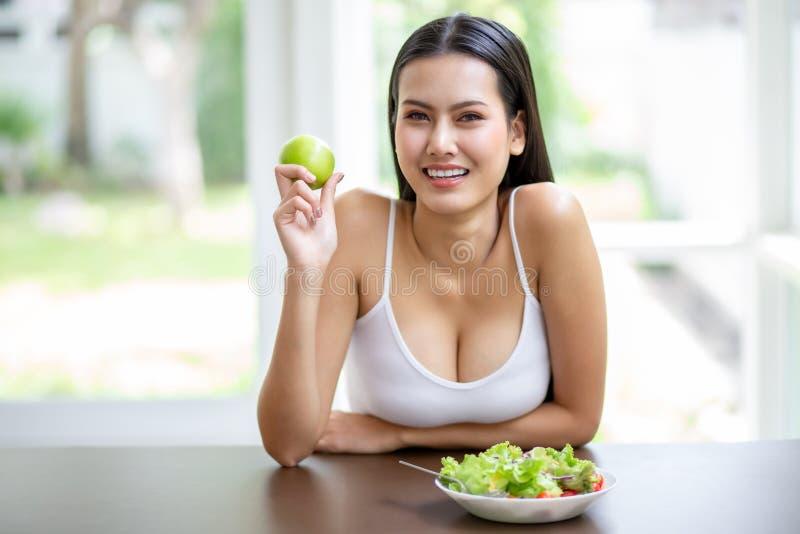 幸福性感的亚洲年轻女人,带着白色单线微笑,拿着绿苹果,吃新鲜的有机沙拉 美女 图库摄影