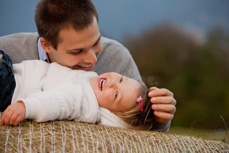 幸福是他的小女儿迷惑的父亲 图库摄影
