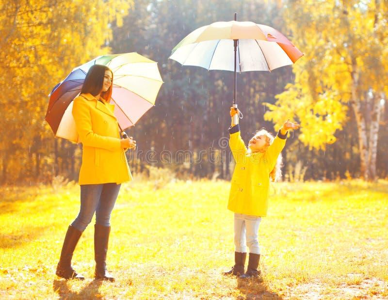 幸福的片刻!与伞的愉快的家庭晴朗的秋天雨天、年轻母亲和孩子夹克的户外 免版税库存照片