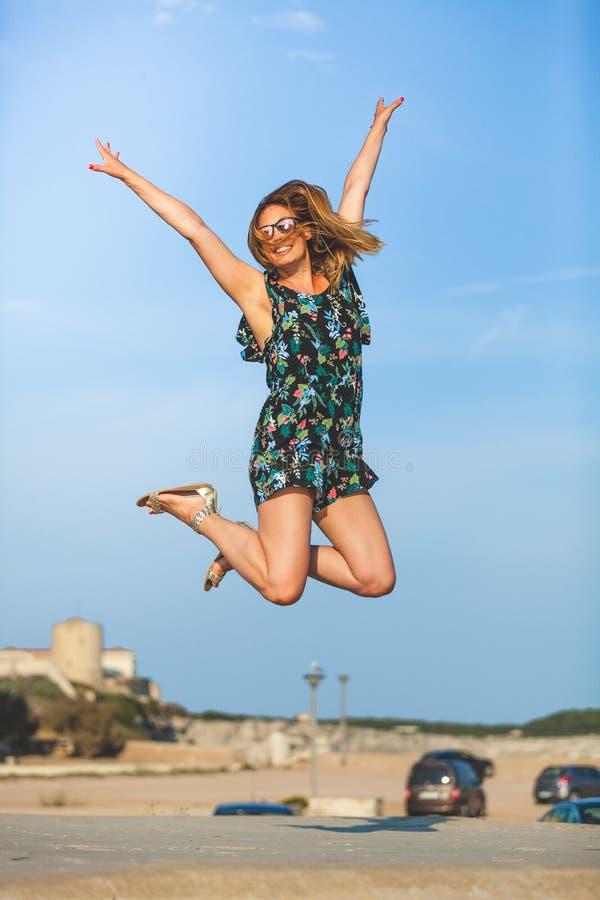 幸福飞跃  快乐和微笑的少妇跳与被举的胳膊 免版税库存照片