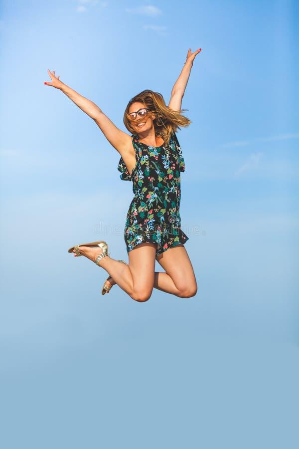 幸福飞跃  快乐和微笑的少妇跳与被举的胳膊 库存照片