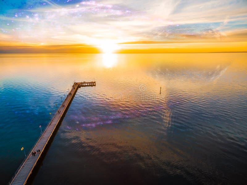 幻想风景-观看在海的人们美好的日落码头的 免版税库存图片