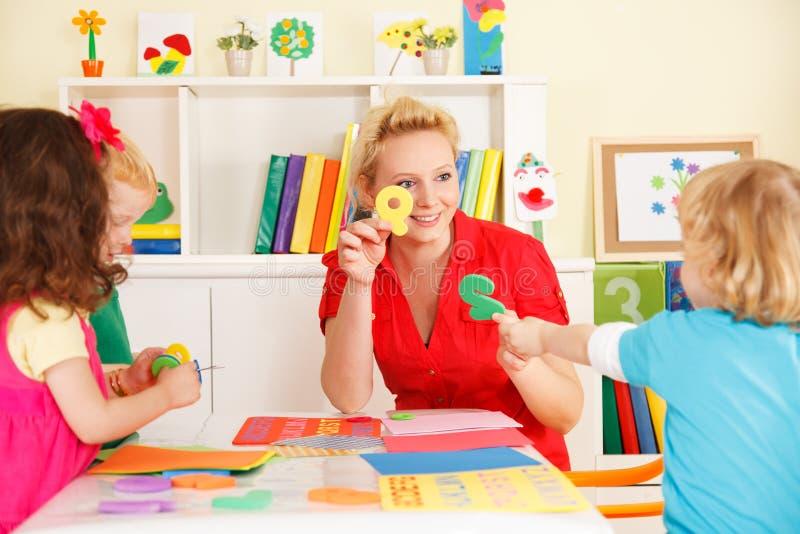 幼儿园孩子在有老师的教室 免版税图库摄影