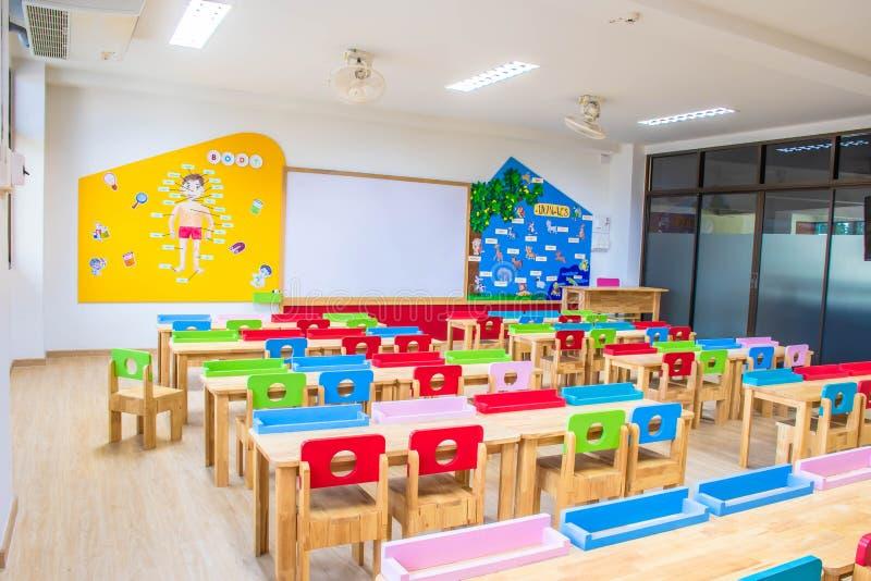 幼儿园教室里的桌椅和白板 还有装饰精美的知识板 库存图片