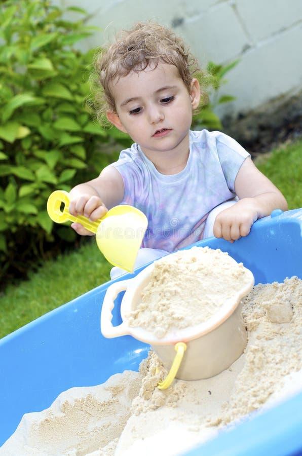 幼儿,女孩,使用与桶和小铲。 库存照片