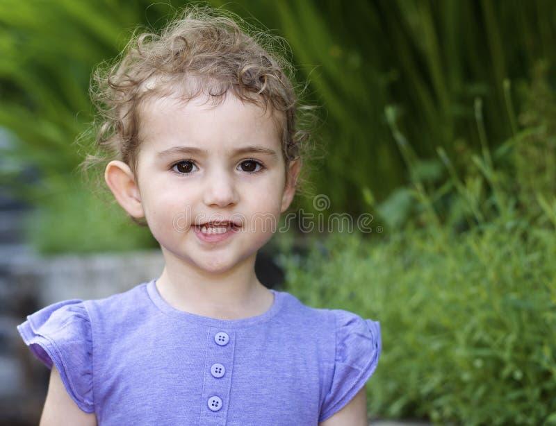 幼儿,女孩,看直接照相机的淡紫色上面的。 免版税库存图片