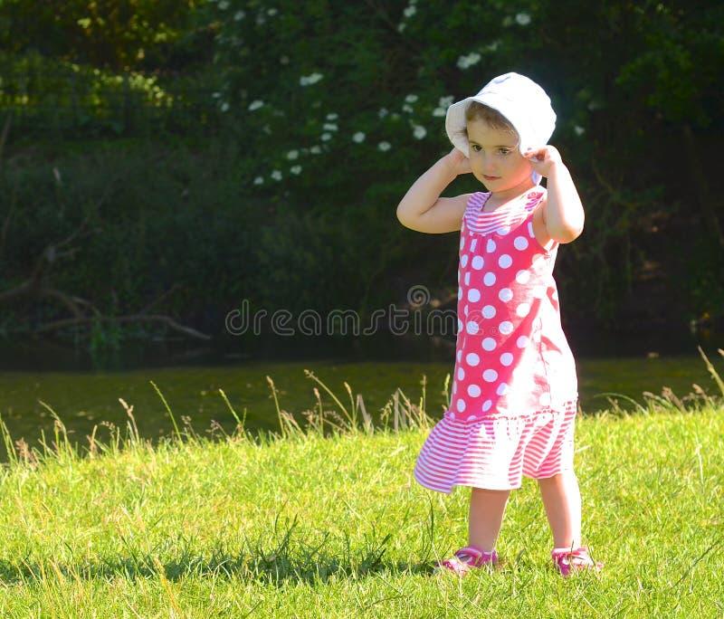 幼儿,拿着帽子的女孩。 免版税库存图片