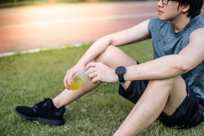 幼小亚洲人赛跑者饮用的能量饮料在跑在Th以后 免版税图库摄影