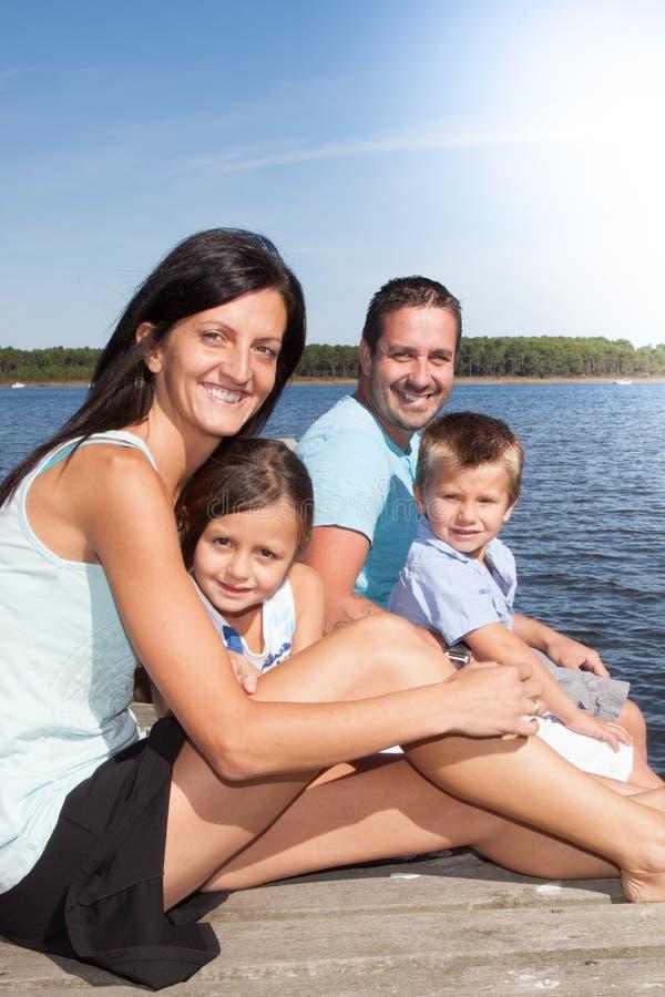 幼小四口之家在海滩浮船 免版税库存照片