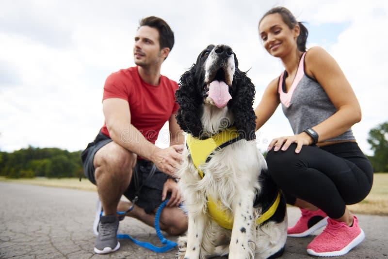 幼小夫妇和狗在锻炼以后 免版税库存照片