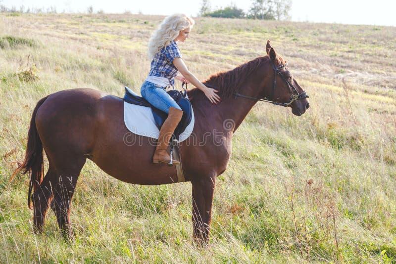 幼小美丽的金发妇女骑乘马画象  与动物的旅行 库存照片