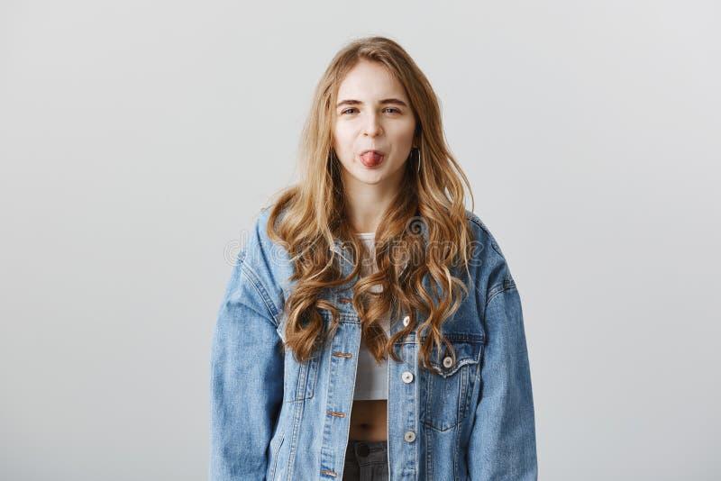幼稚女孩不喜欢您 无礼可爱的妇女室内射击显示舌头的牛仔布夹克的,表达 免版税库存照片