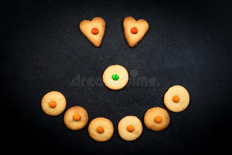幼稚曲奇饼的兴高采烈的面孔在黑背景的 免版税库存图片