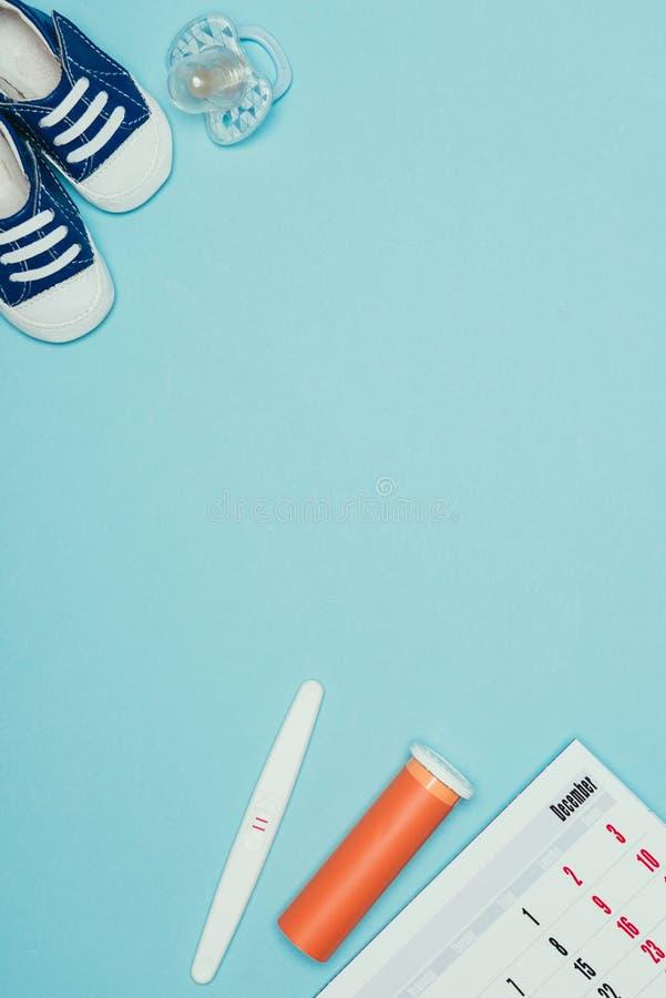 幼稚鞋子、安慰者、日历、妊娠试验和避孕顶视图  库存照片