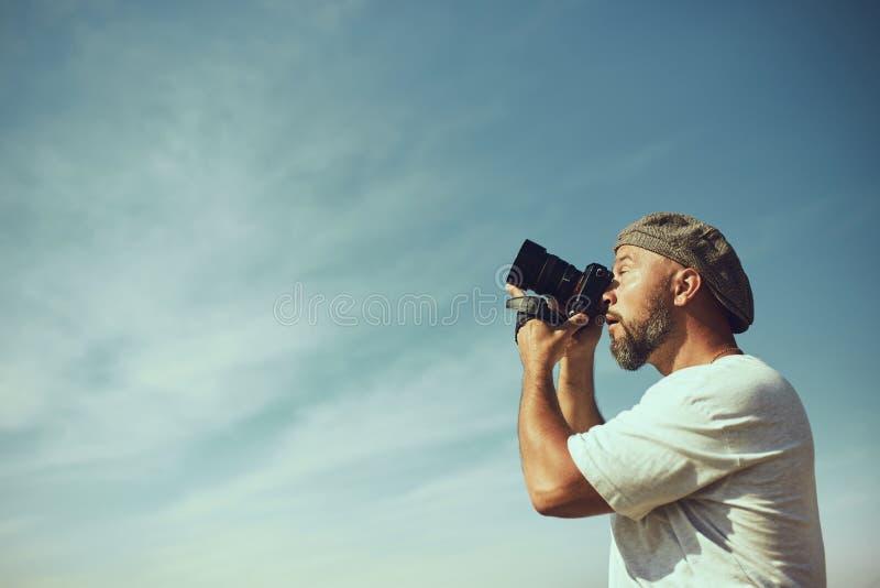 幽默概念 一位非常情感摄影师为某事照相在空气 惊奇的情感在他的面孔的 免版税库存图片