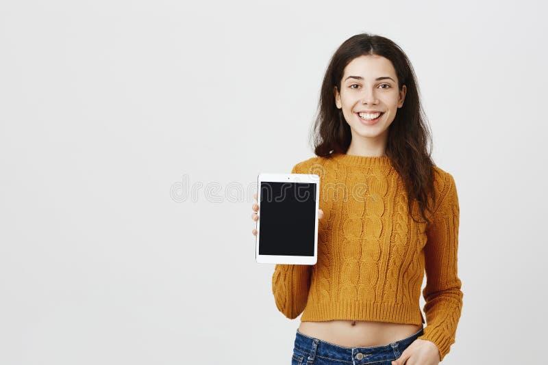 广告和人面表示概念 拿着片剂的年轻可爱的妇女显示它在照相机,当时 免版税库存图片