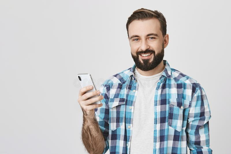 广告和技术概念 手中英俊的欧洲男性式样举行的智能手机,当微笑cheerfuly时 库存图片