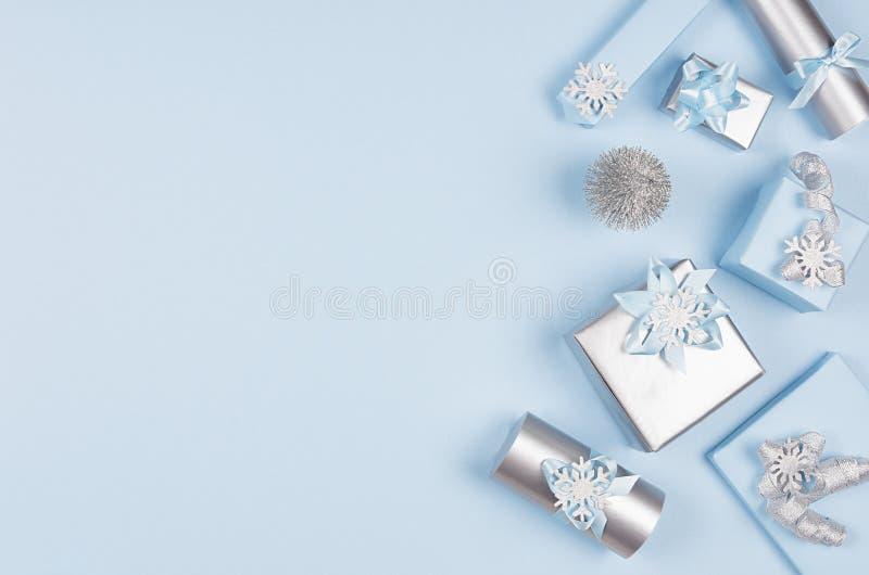 广告和设计的冬天欢乐背景-设置有丝带的蓝色和银色金属礼物盒在软的蓝色 免版税库存照片
