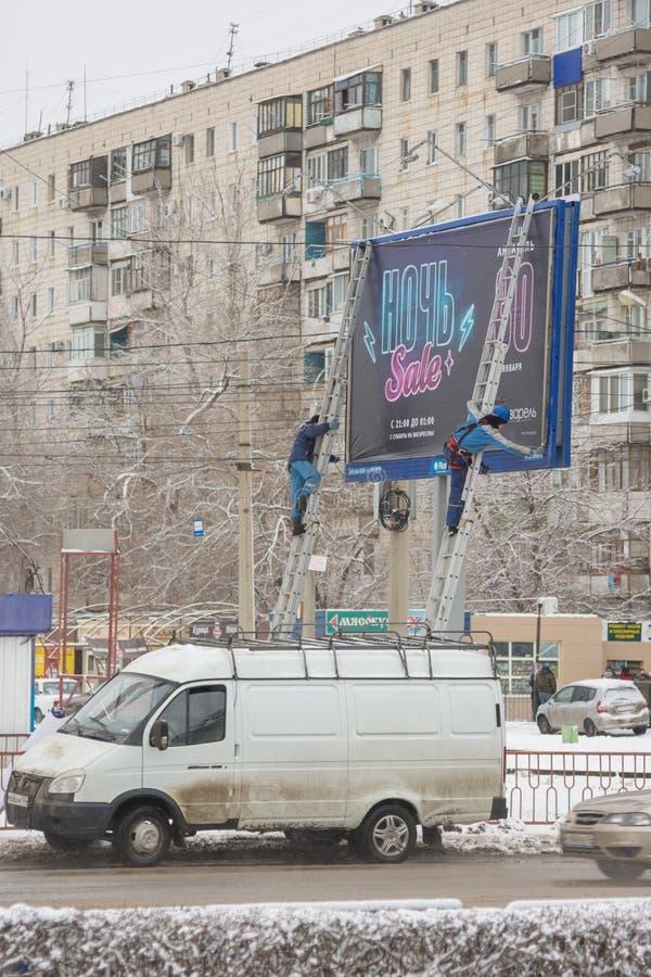 广告商浆糊横幅的雇员在街道广告牌的 图库摄影