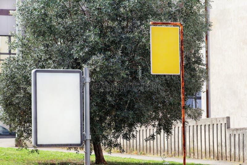 广告牌和黄色广告在街道城市、绿色植物、选择聚焦和特写镜头上 空白的广告显示 免版税库存图片
