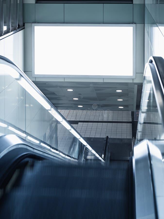 广告牌在与自动扶梯的地铁站嘲笑了  免版税库存图片