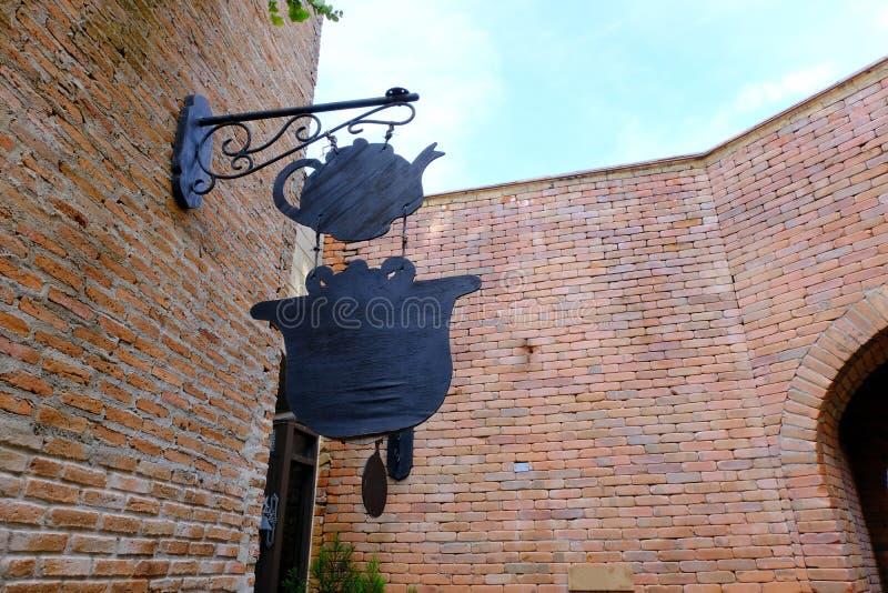 广告牌在砖墙引导垂悬茶的餐馆的岗位标志 免版税库存图片