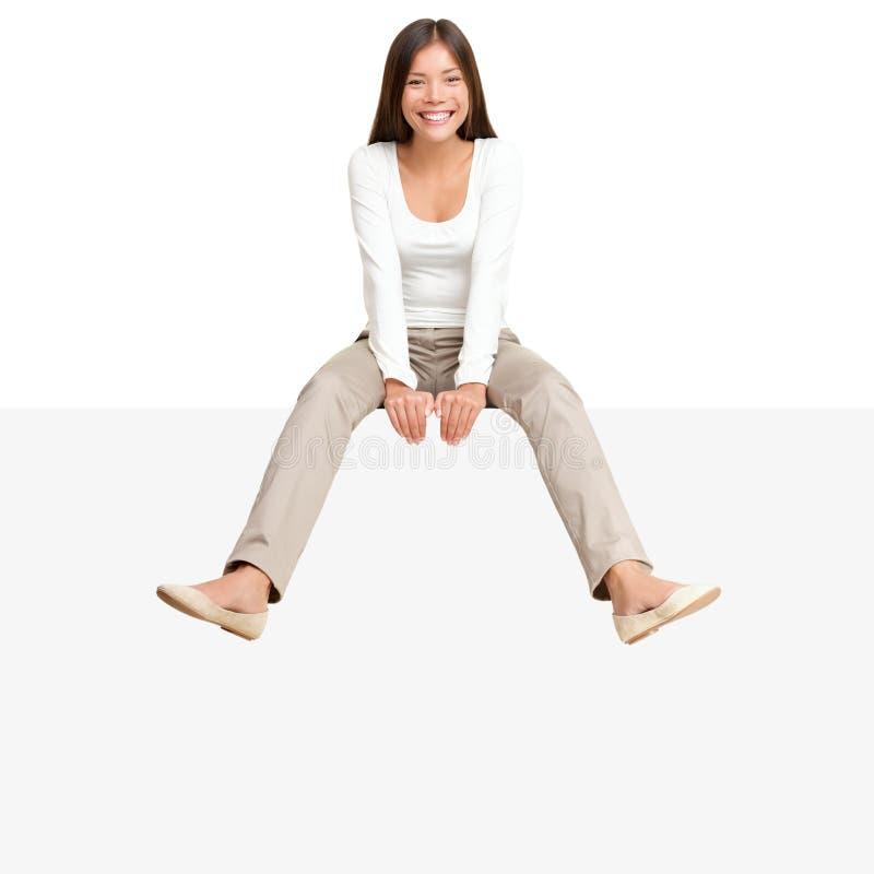 广告牌边缘符号坐的妇女 图库摄影
