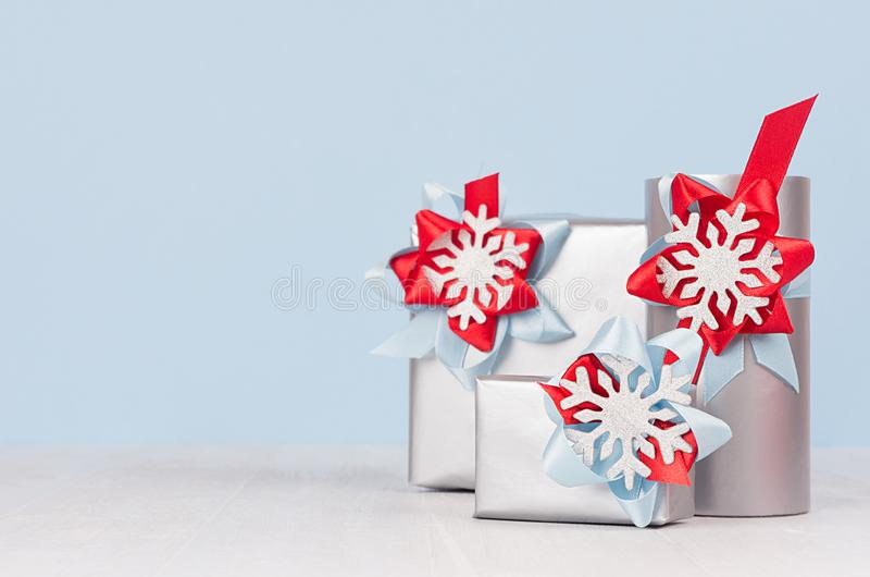 广告的冬天季节典雅的冷的背景和设计-有红色和蓝色丝绸丝带的,弓银色礼物盒 库存照片