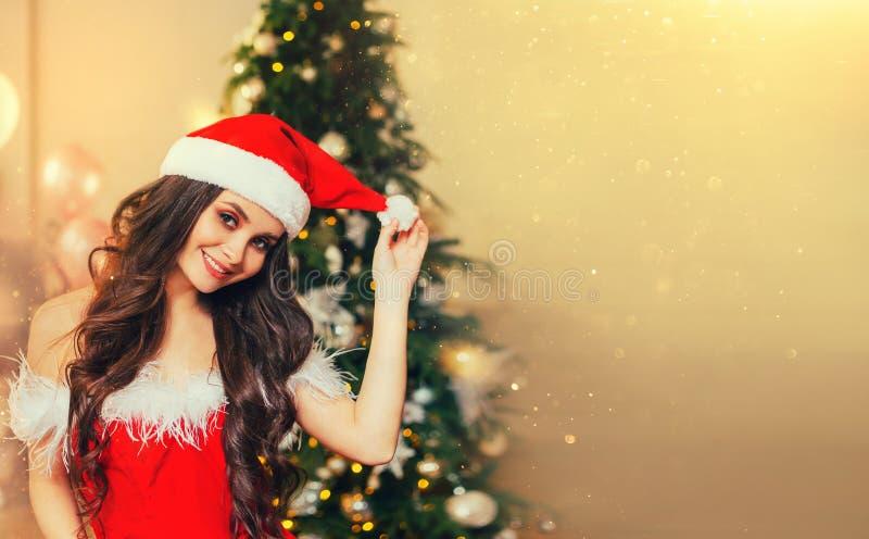 广告的美妙的讨人喜欢的背景或公告,有黑发的俏丽的女孩在一套红色圣诞老人项目衣服 库存照片