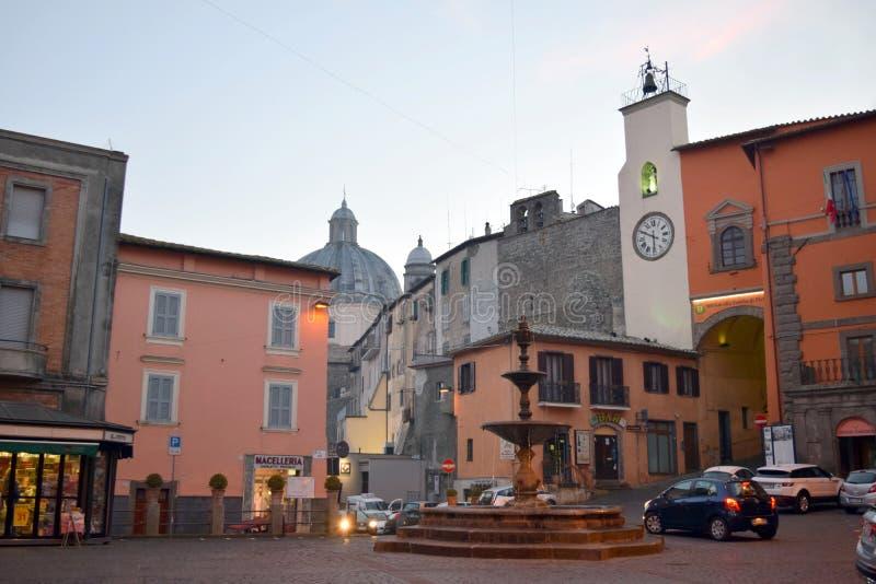 广场维托里奥・埃曼努埃莱・迪・萨伏伊喷泉和时钟,蒙泰菲亚斯科内,维泰博,意大利 库存照片