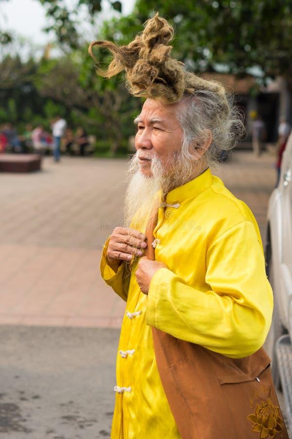 广宁省,越南- 2015年3月22日:老越南人画象有非常长的头发的 他穿佛教衣裳的` s 免版税库存图片
