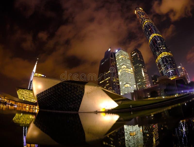 广州中国,2019年6月06日:广州歌剧院的夜风景有反射的与水和城市摩天大楼那 图库摄影