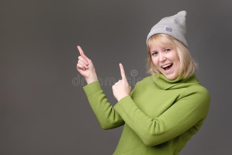 广泛地微笑对照相机的白肤金发的年轻女人,指向手指,显示有趣的事 图库摄影