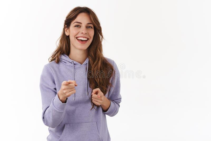 广泛地微笑快乐的少女指向手指照相机的友好的无忧无虑的注视发笑有欢乐的正面 免版税库存照片