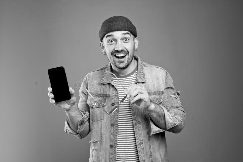 广泛地微笑欢乐的时髦的人画象,当显示他的智能手机时 图库摄影