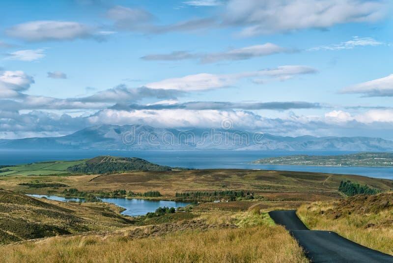 庄严阿伦岛作为日出反射与清楚的蓝天的山与做剧烈的白色云彩scen 图库摄影