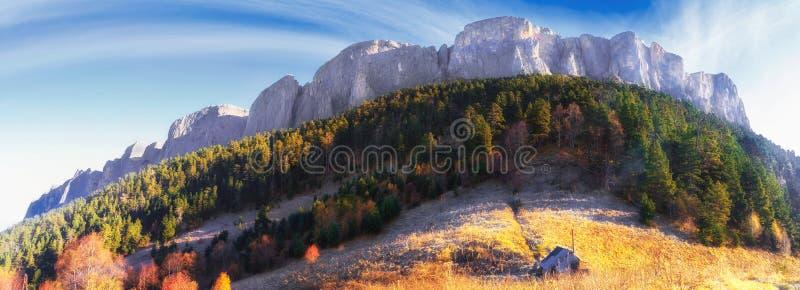 庄严Bolshoy Tkhach落矶山脉峰顶美好的风景金黄秋天风景在日出的蓝天下与木游览 免版税库存照片